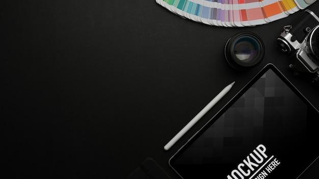 Vista dall'alto del tavolo nero con mockup tablet e campione di colore