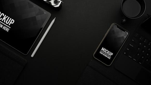 Vista dall'alto del tavolo nero con tablet e smartphone mockup