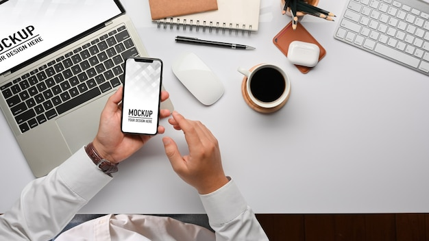 Vista dall'alto delle mani di uomo d'affari utilizzando il modello di smartphone
