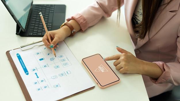 Vista dall'alto della donna di affari che lavora con documenti cartacei e schermata di mockup dello smartphone