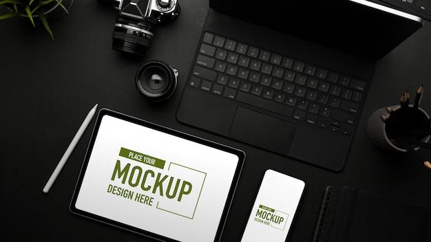 Vista dall'alto dell'area di lavoro piatta creativa scura con fotocamera smartphone tablet