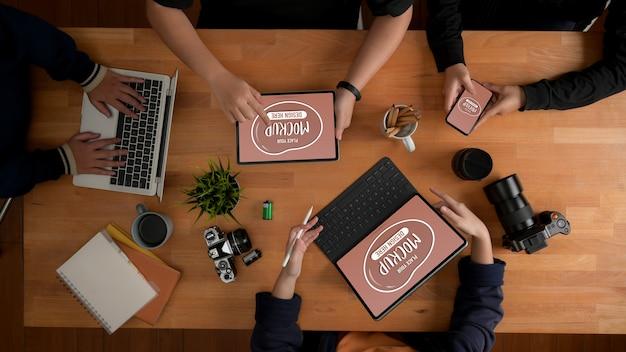 Vista dall'alto del briefing del team di designer sul progetto con mockup di dispositivi