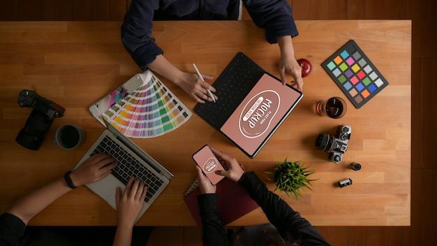 Vista dall'alto del team di designer che lavora insieme al loro progetto con mockup di dispositivi digitali