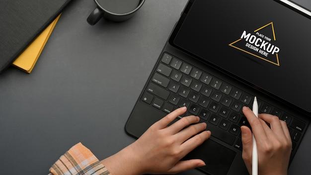 Vista dall'alto delle mani femminili freelance che digitano sul modello di tablet