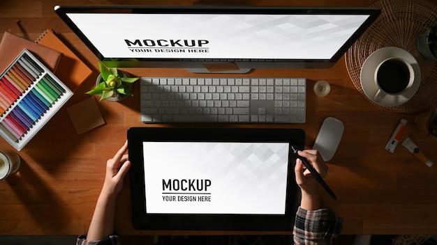 Vista dall'alto del designer grafico femminile che lavora con tablet, computer e mockup di materiali di consumo