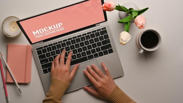 Vista superiore della mano femminile che lavora con il mockup del computer portatile, la tazza di caffè e il vaso di fiori sul tavolo
