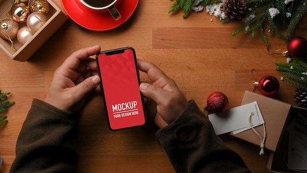 Vista dall'alto della mano che tiene il mockup dello smartphone e le decorazioni di natale