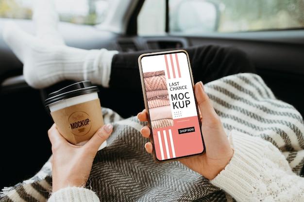 Vista dall'alto a portata di mano con mockup di smartphone e tazza di caffè