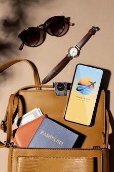 Vista dall'alto sugli articoli per viaggiare con il mockup del telefono