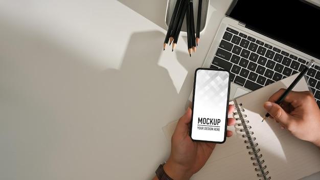 Vista superiore della mano maschio che scrive sul taccuino in bianco e che tiene il modello dello smartphone