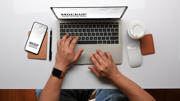 Vista dall'alto delle mani maschili che digitano sul modello di tastiera del computer portatile