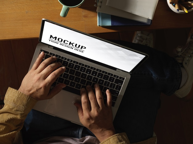 Vista dall'alto delle mani maschili che digitano sul modello di laptop