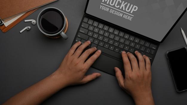 Vista dall'alto delle mani maschili che digitano sulla tastiera mockup tablet
