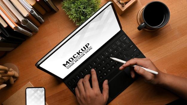 Vista superiore delle mani maschili digitando sulla tastiera del tablet mockup sul tavolo di studio in legno