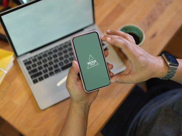 Vista dall'alto del lavoratore di sesso maschile utilizzando mock up smartphone sopra il tavolo da lavoro mentre era seduto in ufficio