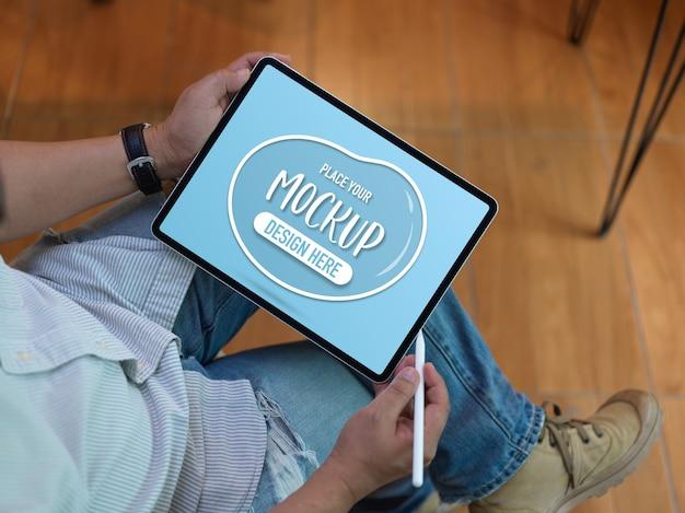 Vista dall'alto del lavoratore di sesso maschile utilizzando tablet mock-up