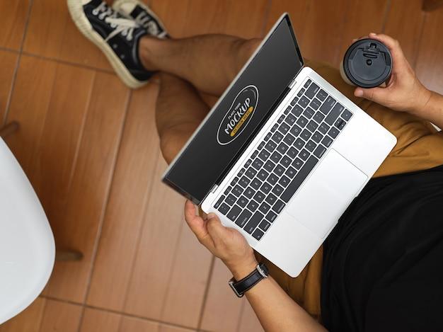 Vista dall'alto dell'uomo che si distende nella sua stanza mentre tiene mock up computer portatile e tazza di caffè