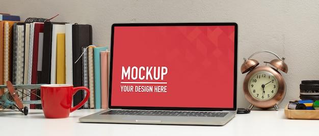 Vista dall'alto del laptop mockup sul tavolo di studio con elementi e decorazioni della scuola