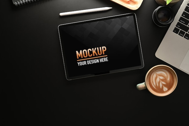 Vista dall'alto della scrivania da ufficio con mock up tablet, tazza di caffè, laptop e copia spazio