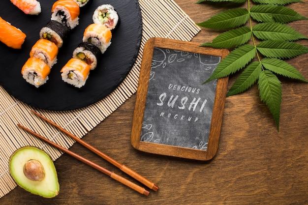 Vista dall'alto della varietà di sushi con lavagna e avocado