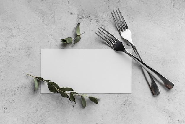 Vista dall'alto della disposizione dei tavoli con mock-up e forchette del menu primaverile