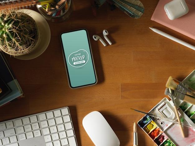 Vista dall'alto del tavolo in legno con mock up smartphone, tastiera, strumenti di pittura e forniture