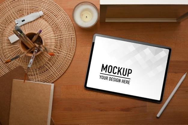 Vista dall'alto del tavolo in legno con mockup tablet con cancelleria
