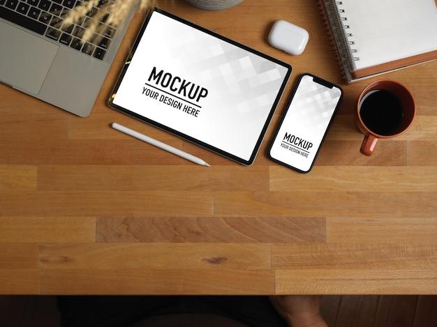 Vista dall'alto del tavolo da lavoro in legno con mockup di tablet e smartphone