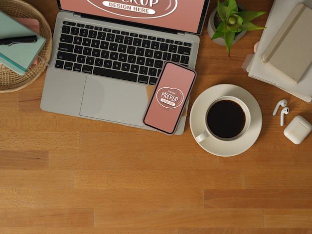 Vista dall'alto dell'area di lavoro con mock up laptop, smartphone, tazza di caffè, cancelleria e copia spazio
