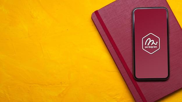 Vista dall'alto dell'area di lavoro con mock up smartphone, taccuino rosso e spazio di copia