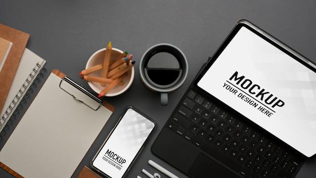 Vista dall'alto dell'area di lavoro con tastiera tablet e mockup smartphone