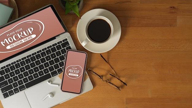 Vista dall'alto del piano di lavoro con mock up laptop, smartphone, occhiali, tazza di caffè e spazio di copia