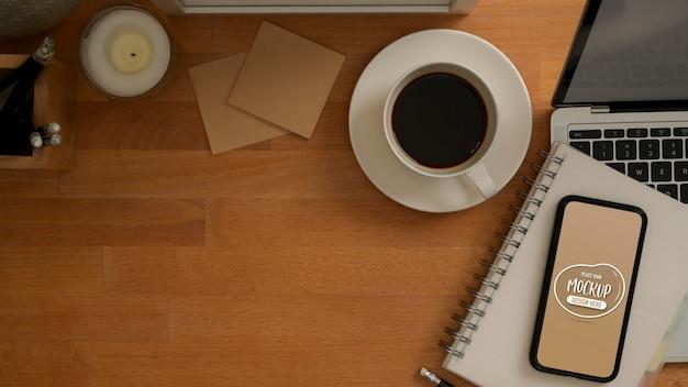 Vista dall'alto del piano di lavoro con mock up di smartphone, laptop, tazza di caffè, cancelleria e spazio di copia