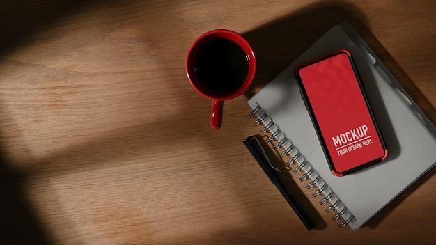 Vista dall'alto del piano di lavoro con mockup di smartphone, taccuino, penna e tazza di caffè