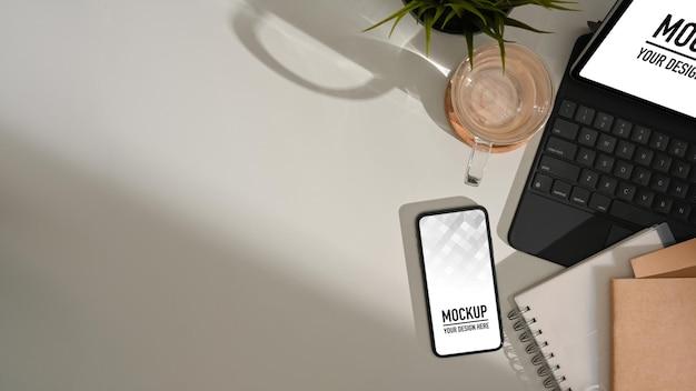 Vista dall'alto del piano di lavoro con il mockup dello smartphone