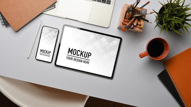 Vista dall'alto del tavolo da lavoro con mockup di tablet e smartphone