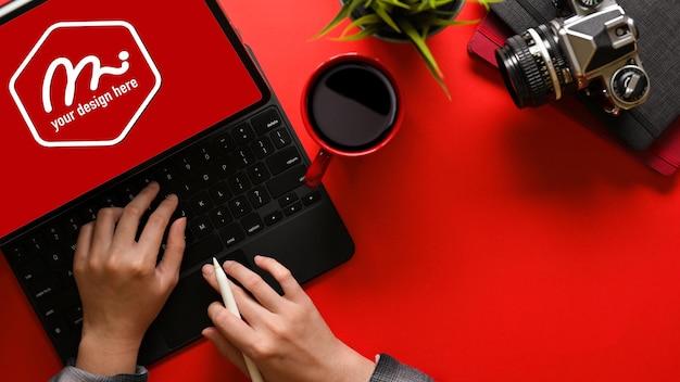 Vista superiore della giovane donna che digita sul tablet mockup sulla scrivania rosso brillante con spazio di copia include il tracciato di ritaglio