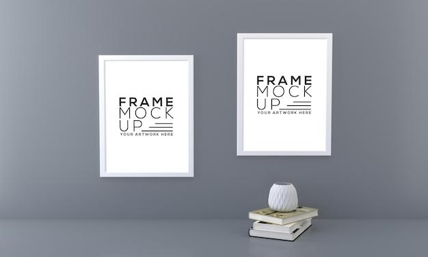 Mockup a due cornici con libri e vaso su un'opera d'arte di presentazione della parete scura 3d rendering