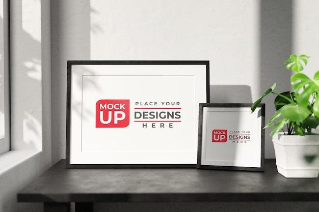 Due foto o poster con cornice orizzontale sul tavolo di legno