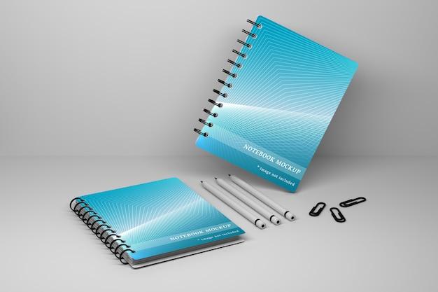 Di due quaderni di quaderni a spirale per ufficio, tre matite di carbonio e perni di carta