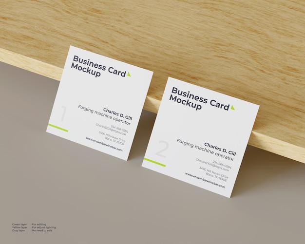 Un modello quadrato di due biglietti da visita si appoggia contro il legno