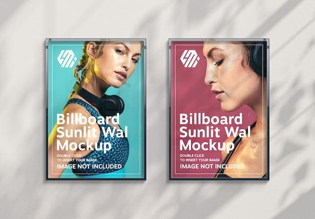 Due cartelloni pubblicitari verticali che appendono sulla parete illuminata dal sole mockup