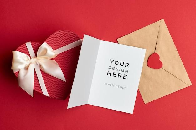 Mockup di carta di san valentino con busta e confezione regalo di cuore su rosso
