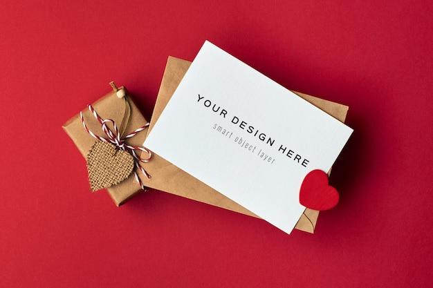 Mockup di carta di san valentino con scatola regalo decorata a cuore su rosso