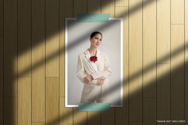 Modello di foto con cornice di carta verticale con sovrapposizione di ombre della finestra e sfondo in legno
