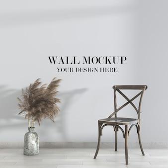 Mockup di parete all'interno con sedia con schienale incrociato in legno rustico