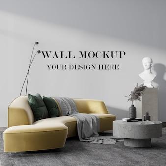 Mockup di parete dietro divano giallo e scultura