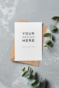 Mockup di biglietto di auguri di matrimonio con busta e ramoscelli di eucalipto su grigio