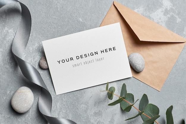 Mockup di carta di invito a nozze con busta, ramoscello di eucalipto e pietre grigie