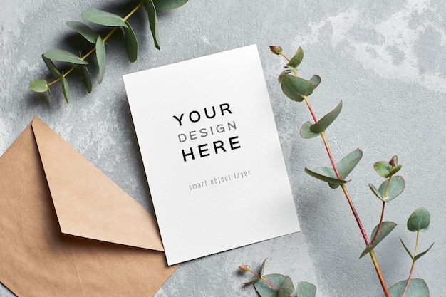 Mockup di carta di invito a nozze con busta e ramoscello di eucalipto